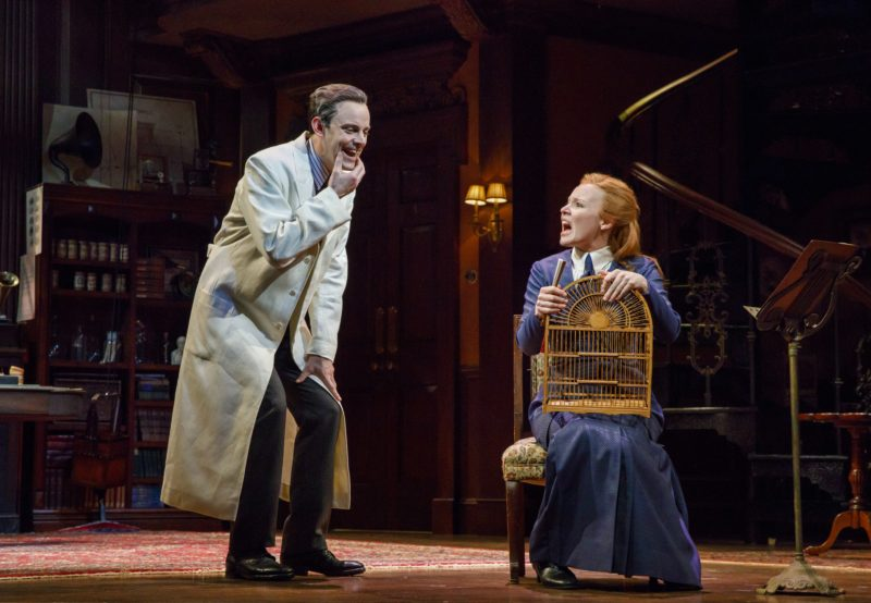 Professor Higgins dressed in his lab coat, holds his jaw to enunciate a phrase while Eliza Doolittle observes sitting in a chair.